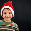 Kid portrait with christmas hat on black background. With copy space — Stock Photo
