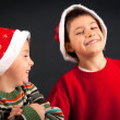 Stock Photo: Two brothers playing together with Christmas hat on black background