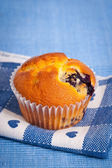 Blueberry muffin on heart napkin and a blue placemat — Stock Photo