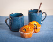 Blueberry muffins and cups on blue placemat — Stock Photo