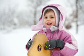 Young girl playing with rocking chair in the snow — Stock Photo