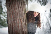 Portrait of beautiful girl in the snow hiding behind a tree — Stock Photo