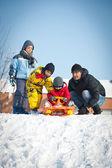 Família feliz se divertindo na neve com bob — Foto Stock