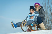 Mother and son sliding in the snow — Stock Photo