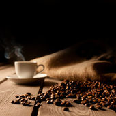Coffee background with beans and white cup. Dark atmosphere — Stock Photo