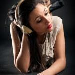 Beautiful girl listening to music against dark background — Stock Photo #15370537