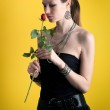 Portrait of romantic girl with rose flower and black dress against yellow background — Stock Photo