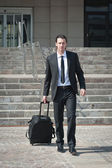 Young business man with suitcase — Stock Photo