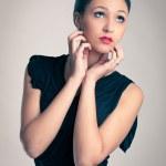 Elegant woman in black dress against beige background — Stock Photo