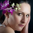 Close up portrait of beautiful girl with orchid pink flower — Stock Photo