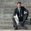 Young business man with newspaper sitting on the stairs — Stockfoto