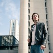 Young casual man portrait with building background - Lizenzfreies Foto