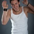 Athletic young man wearing jeans and white singlet against dark background — Stock Photo #15654507