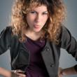 Portrait of beautiful curly girl posing against grey background — Stock Photo