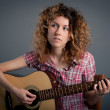 Country girl with a guitar singing against dark background — Stock Photo