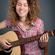 Happy country girl with a guitar against dark background — Stockfoto