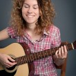 Happy country girl with a guitar against dark background — Stok fotoğraf
