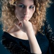 Portrait of beautiful curly girl with black lace dress against dark background — Stock Photo