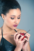 Conceptual image of beautiful girl with nails driven apple — Stock Photo