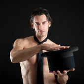Young magician shirtless with cylinder against black background — Stock Photo