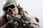 Soldier with rifle against white background. Shallow depth of field — Stockfoto
