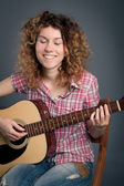 Happy country girl with a guitar against dark background — Stock Photo