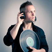 Young man working as dj with ear-phones and disc — Stock Photo