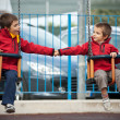 Two brothers swinging together — Stock Photo