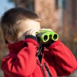 Portrait of a young boy with binoculars. Lateral view - Stock Photo