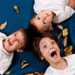 Three kids - 6 and 4 year old - laughing, lying on autumn leaves — Stock Photo