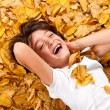 6 years kid laughing, lying on autumn leaves — Stock Photo