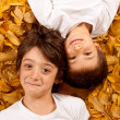 Stock Photo: Two kids - 6 year old - laughing, lying on autumn leaves