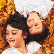 Two kids - 6 year old - laughing, lying on autumn leaves — Stock Photo