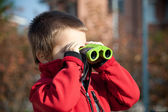Portrait of a young boy with binoculars. Lateral view — Stock Photo