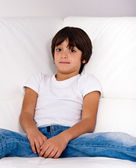 6 years old kid lying on white sofa, portrait — Stock Photo