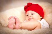 Four months old baby with red hat. Focus on feet — Stock Photo