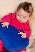 Four months old baby holding blue heart — Stock Photo