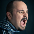 Man portrait with angry expression on dark background — Stock Photo