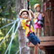 6 year old kids climbing trees in Dolomites, Italy - Stock Photo