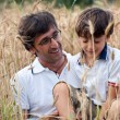 Father playing with his son in a wheat field — Stock Photo