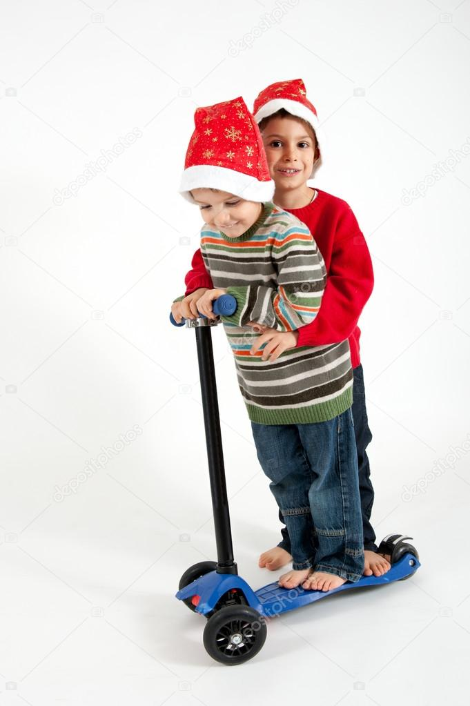 Two Brothers playing together with christmas hat and scooter on white background — Stock Photo #16290077