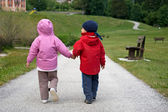 Girl and boy walking holding hands — Stock Photo