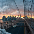 Panoramic shot of Manhattan skyline from the Brooklyn bridge at dusk - Stock Photo