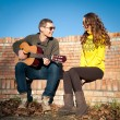 Romantic young couple portrait playing guitar under blue sky — Stock Photo #18446397