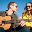 Romantic young couple portrait playing guitar under blue sky - Stock Photo