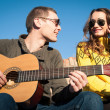 Romantic young couple portrait playing guitar under blue sky — Photo