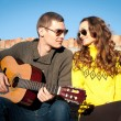 Romantic young couple portrait playing guitar under blue sky — Stock Photo