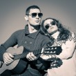 Romantic young couple portrait playing guitar. Sepia tone image — Stock Photo