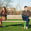 Angry young couple sitting away outdoors on a bench — Stockfoto