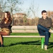 Angry young couple sitting away outdoors on a bench — Stock Photo #18446433